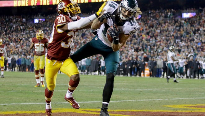 Philadelphia Eagles wide receiver Riley Cooper (14) pulls in a touchdown under pressure from Washington Redskins free safety E.J. Biggers (30) during the second half of the game Saturday.
