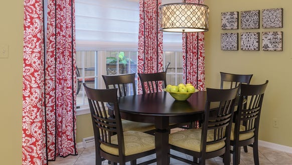 The dining area features red patterned panels and apple-green