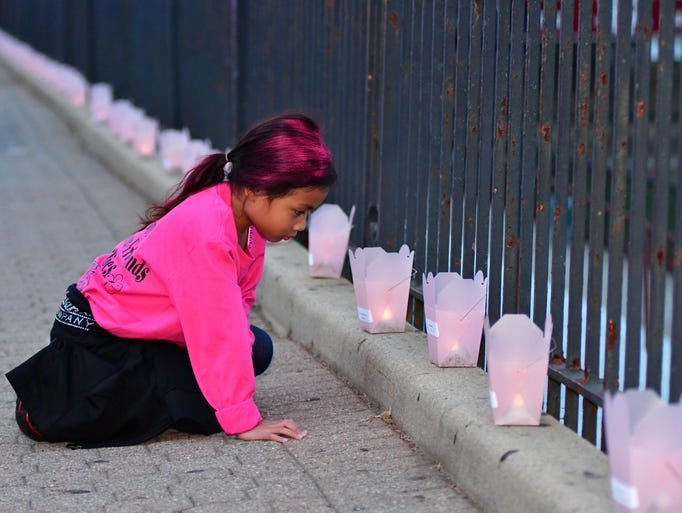 Kali Aguirre kneels at the luminaries during the Nutley