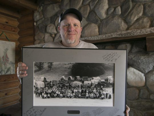 "In this Monday, Jan. 14, 2019 photo, Kenny Lindsay, owner/auctioneer of Kenny Lindsay's American Eagle Auctions and Appraisals Co., holds an original cast and crew photo from the production of the television show, ""Little House on the Prairie,"" in Genoa Township, Mich. The photo sold for $1200 to the Laura Ingalls Wilder Museum from the estate of Melissa Gilbert and Timothy Busfield."