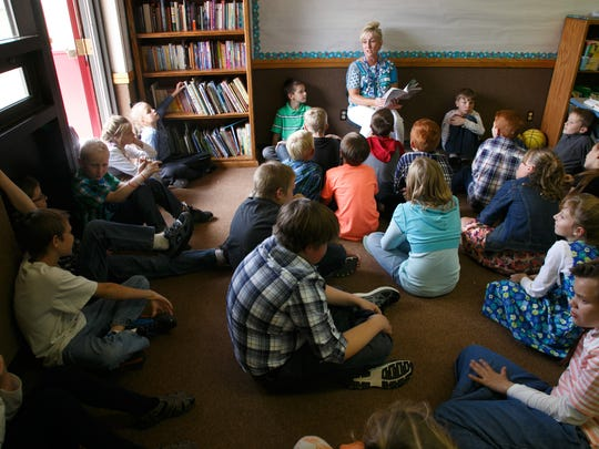 Water Canyon School elementary students listen as their teacher, Suzanne Lytle reads to the class on the first day of school Monday in Hildale.