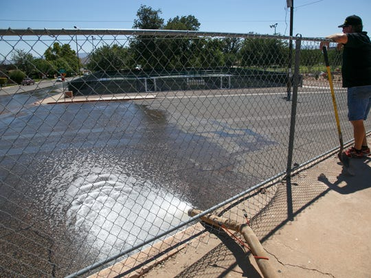 Lion's Club member Bryce Christensen watches flood water flow down 400 East Street in St. George as it's pumped out of the Sunbowl and into the roadway Thursday, Aug. 28, 2014. More rain was expected to hit Washington County the early part of this week.