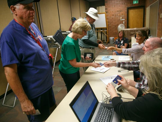 Election workers checks identification, sign in voters and take back voting machine cards at the St. George City Offices Tuesday, Oct. 21, 2014 on the first day of early voting in Utah.