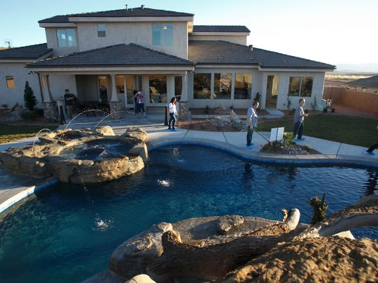 "Visitors to the St. George Area Parade of Homes entry called ""The True Home"" look walk through the back yard past a pool with a log slide and afire feature built in Friday, Feb. 13, 2015 on the opening day of the 2015 parade."