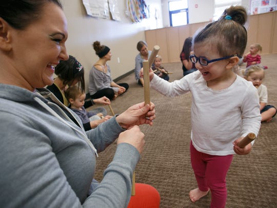 Heather Stott, left, taps sticks in time to music with