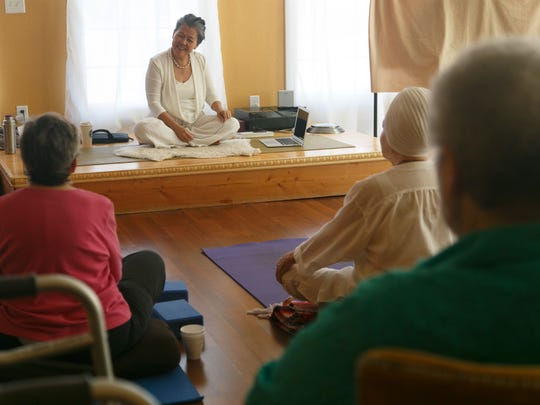 Benja Peterson discusses the class and gives participants tips on getting comfortable at the beginning of her breath work and meditation class at Benja's Downtown Yoga Studio on Friday.