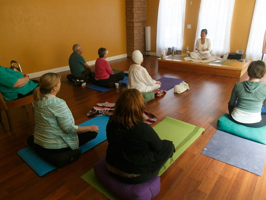 Participants sit on yoga mats, on cushions and in chairs as Benja Peterson leads her breath work and meditation class at Benja's Downtown Yoga Studio on Friday.