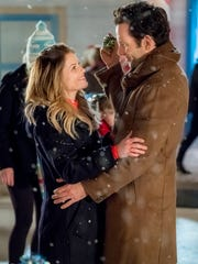 Candace Cameron Bure (with Eion Bailey) plays twin sisters Kate and Chris who switch lives before Christmas.