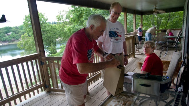 Bob Clift, left, breads fish while talking with sister Barb Francis and her husband during a Memorial Day get together at the Francis home in Bella Vista, Ark. Dick and Barb Francis retired to Arkansas from California about 10 years ago.