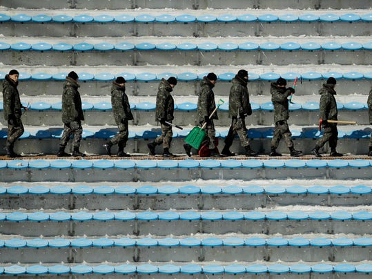Soldiers carry shovels and picks as they clear snow and ice from the seating area at the Alpensia Ski Jumping Center ahead of the 2018 Winter Olympics in Pyeongchang, South Korea, Wednesday, Feb. 7, 2018. (AP Photo/Charlie Riedel)