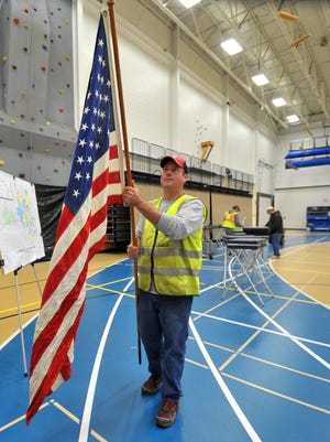 Matt Baker unfurls a flag Monday to be posted at the polling place at Wausau West High School for Tuesday's statewide elections.