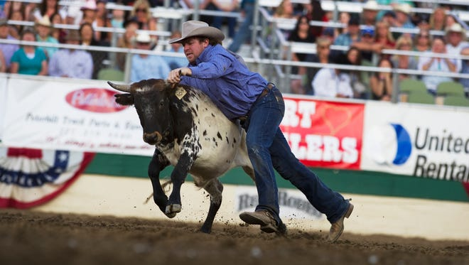 Forest Sainsbury of Camp Crook, S.D., tries to bring a steer to the ground during the Steer Wrestling competition at the Reno Rodeo on Saturday, June 21, 2014 in Reno, Nev.