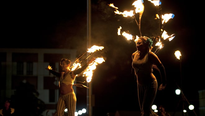 Members of the fire performance group Obsidian Butterfly, Adrienne Deciur, left, and Marla Santoyo, performed on Saturday, July 26, 2014 in downtown Reno, Nev., during the Reno Compression event.