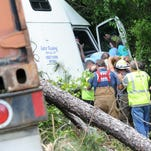 Emergency officials work extract the driver of an 18-wheeler after wrecking near mile marker 55 on Interstate-59 South Thursday.