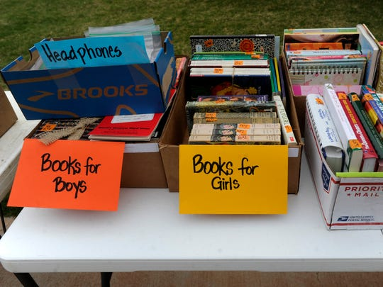 Books sit out on display to be picked through at a multi-family garage sale on Saturday, April 1, 2017, in south Abilene.