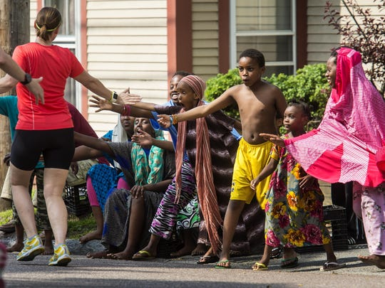 Kids high-five runners on Pine Street during the People's United Bank Vermont City Marathon in Burlington on Sunday, May 29, 2016.
