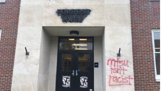 """This photo from Middle Tennessee State University Police shows how a vandal covered """"Forrest Hall"""" name with black spray paint and wrote """"MTSU isn't racist"""" in red spray paint."""