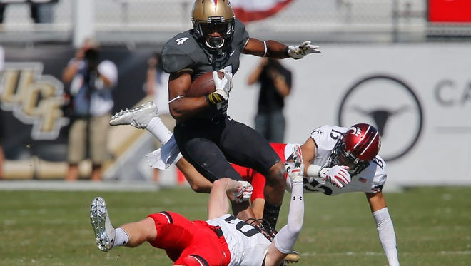 UCF Knights wide receiver Tre'Quan Smith (4) breaks tackles by Cincinnati Bearcats cornerbacks Grant Coleman (13) and Desmond Johnson (10) during the first quarter of a football game at Bright House Networks Stadium.