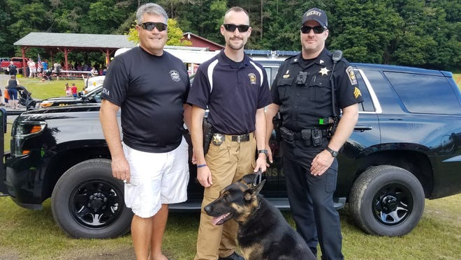 Photo attached, taken by me, at Groton Community Night Out on August 1. K-9 Deputy Odee in the foreground. Standing from left to right are: Undersheriff Brian Robison, Deputy Marc Ninivaggi, Sergeant Jeremy Zigenfus.