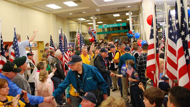 Veterans return to Asheville Regional Airport on Saturday night to a hero's welcome after a day in Washington.