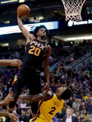 Phoenix Suns guard Josh Jackson, left, shoots over Golden State Warriors center Jordan Bell during the second half of an NBA basketball game in Phoenix, Saturday, March 17, 2018.