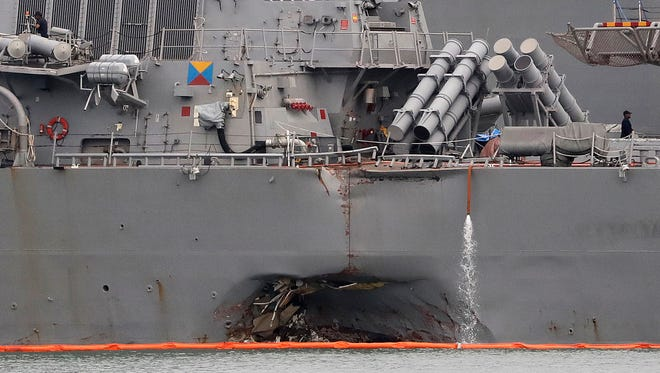 The damaged port aft hull of USS John S. McCain, is seen while docked at Singapore's Changi naval base on  Aug. 22, 2017 in Singapore. The focus of the search for 10 U.S. sailors missing after a collision between the USS John S. McCain and an oil tanker in Southeast Asian waters shifted Tuesday to the damaged destroyer's flooded compartments.
