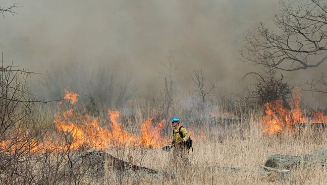 A National Parks Services regional fire management specialist walks past a blaze, Monday, April 10, 2017. The prescribed fire burned 52 acres of Little Round Top at Gettysburg National Military Park. It is the park's biggest controlled burn to date.