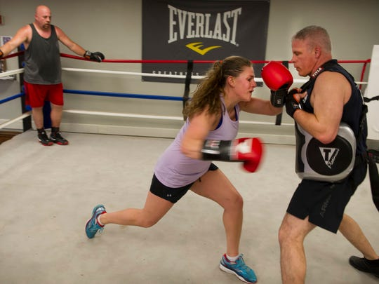 Rachel Gentry, an EMS and volunteer firefighter with the Luce Fire Territory, center, spars with Mike Doran during a workout for the Hoses team at the Old Courthouse basement gym Monday evening.