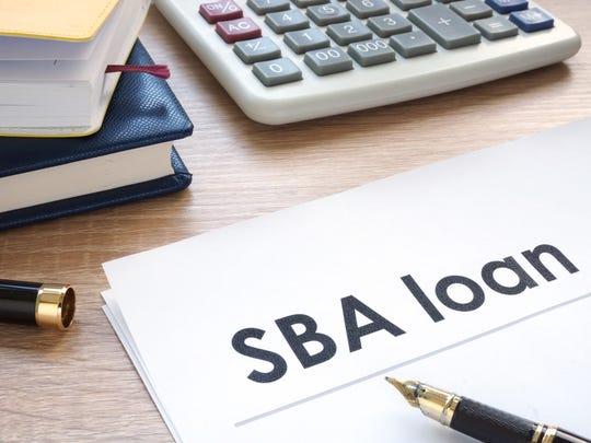 Office desk with calculator and fountain pen over SBA loan headline.