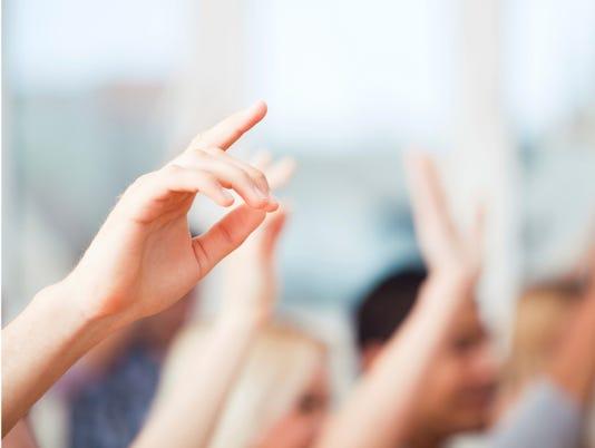 Kids raising hands in school