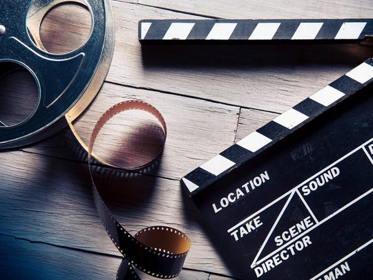 A clapperboard and film reel are positioned on a wooden table.  The film reel is a light metal and is partially unspooled.  Next to it is a black-and-white film slate with the clapper opened.  There is nothing written on the clapperboard.