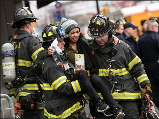 Members of the New York City Fire Department carry an injured person away at the scene of a train derailment at Atlantic Terminal, Wednesday, Jan. 4, 2017, in Brooklyn. A Long Island Railroad train struck a bumping block and derailed, injuring 100 people.