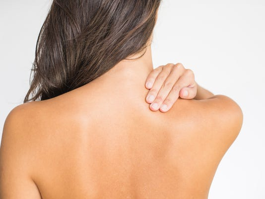 Back view of topless woman with upper back and neck pain