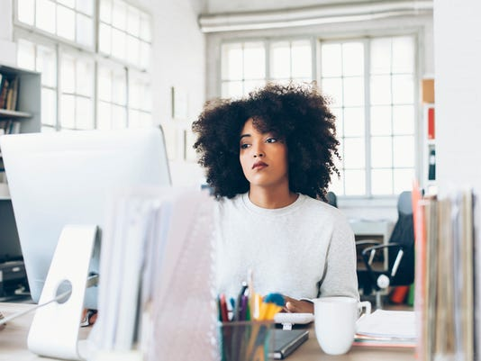 Depressed young woman using computer at the office
