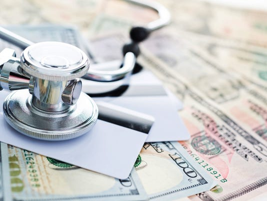 Stethoscope on credit cards and money