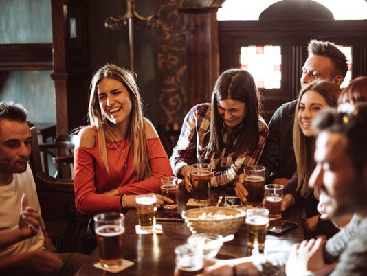 people talking indoors in a pub with the beers