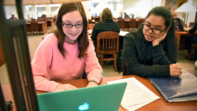 """Students Brittany Mehlhop and Maelyn Soriano collaborate on creating a visual display for the """"Voices of Homelessness"""" project Tuesday, April 5, at St. Cloud State University."""