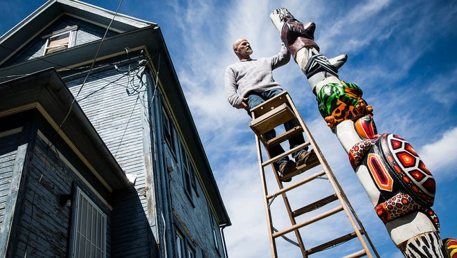 David Mitchell stacks pieces of his totem pole sculpture outside of a home on Main Street Tuesday afternoon.