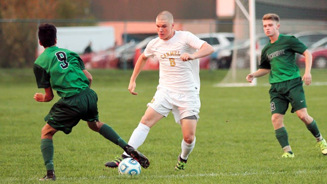 Carmel's Jack Muller tries to dribble the ball past Zionsville's Noah Backhaus.  Carmel defeated Zionsville 1-0 on Wednesday and advanced to Saturday's sectional final.