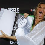 Brazilian model Gisele Bundchen imitates her own gesture as she shows a page of her book, titled Gisele Bundchen, about her 20-year modeling career, before signing autographs in Sao Paulo, Brazil, Friday, Nov. 6, 2015.