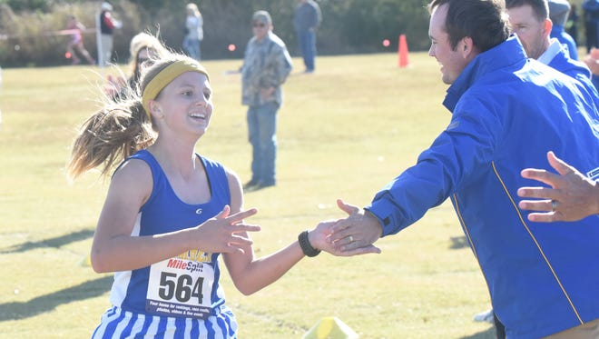 Mountain Home's Marcie Cudworth is congratulated by coaches as she crosses the finish line Tuesday at the 6A-East Conference meet.