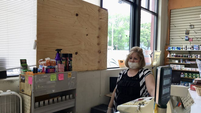 Wanda Rivera behind the counter at her boarded-up store on Main Street in Worcester on Tuesday.