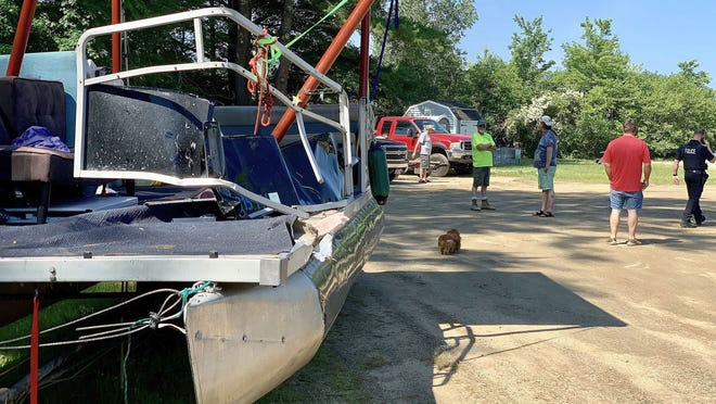 A pontoon boat involved in a late-night crash with another vessel sits in a boat ramp parking lot on Lake Wickaboag in West Brookfield on Sunday.