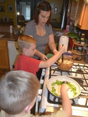 Valerie Spiering helps her sons - 8-year-old Fischer and 5-year-old Larken, foreground - prepare dinner in their Green Bay home Tuesday night, Sept. 13.