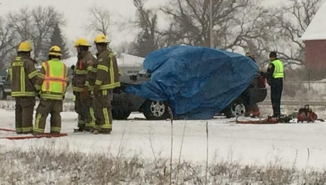 Emergency crews wrap a tarp around a vehicle involved in a crash on southbound U.S. 41 southwest of De Pere on Tuesday morning.