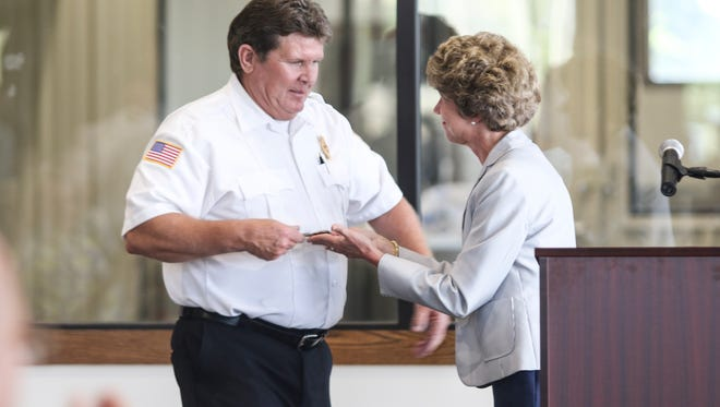 City Mayor Kim McMillan presents Clarksville Fire Rescue Deputy Chief Howell Albright with a key to the city during his retirement ceremony held at Old Glory Distilling Company on Thursday.