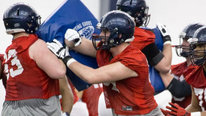 Offensive tackle Alex Givens (center) participates in a spring workout in March. The redshirt freshman has shown good strides throughout the spring.