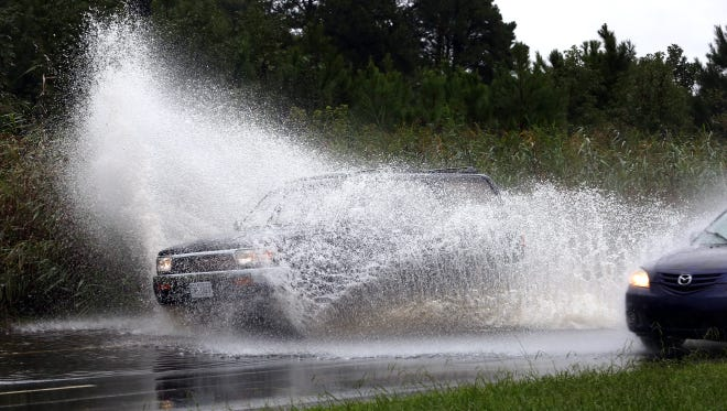 Traffic speeds through floodwaters along Military Highway in Chesapeake, Va., on Sept. 21, 2016. The area was inundated from the remnants of Tropical Storm Julia.