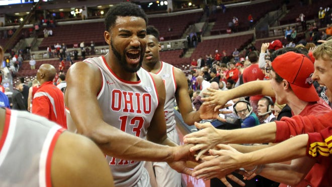 Ohio State Buckeyes guard JaQuan Lyle (13)  of Evansville celebrates with fans following the Buckeyes upset win against the Wisconsin Badgers at Value City Arena. The Buckeyes won 83-73.