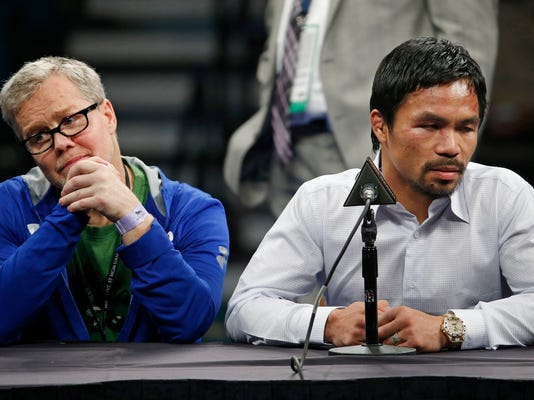 FILE - In this May 2, 2015, file photo, trainer Freddie Roach, left, listens as Manny Pacquiao answers reporter questions during a news conference following Pacquiao's welterweight title fight in Las Vegas. Pacquiao and Roach say their 16-year partnership has ended. Pacquiao disclosed his decision Friday, April 13, 2018, in the final sentence of a news release detailing his plans for his upcoming fight against Lucas Matthysse. (AP Photo/John Locher, File)